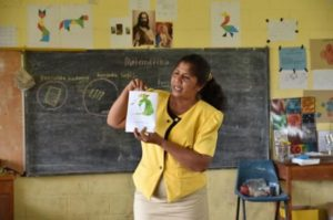 Female Timorese Teacher holding up a book in classroom
