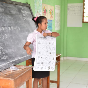 Timorese Teacher standing at front of class with poster